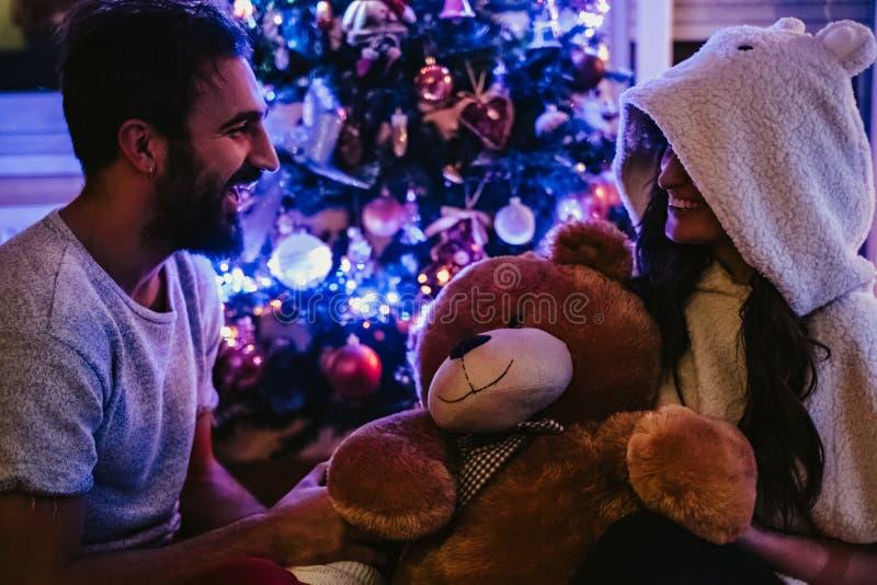 Koppla ihop att skratta framme av julgranen royaltyfria bilder