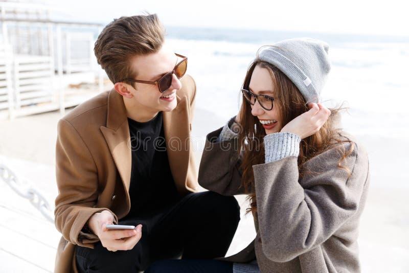 Koppla ihop att skratta och att använda smartphonen tillsammans utomhus i höst arkivfoton