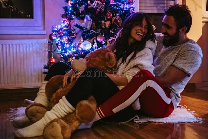 Koppla ihop att skratta och att krama framme av julgranen arkivfoton