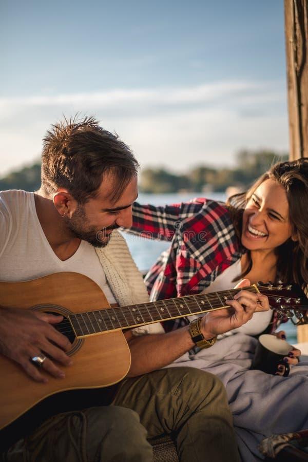 Koppla ihop att skratta och att spela gitarren vid floden royaltyfria foton