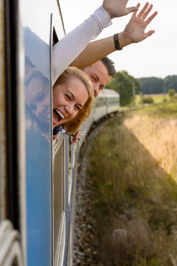 Koppla ihop att skrika ut att vinka för drevfönster som är lyckligt royaltyfri fotografi