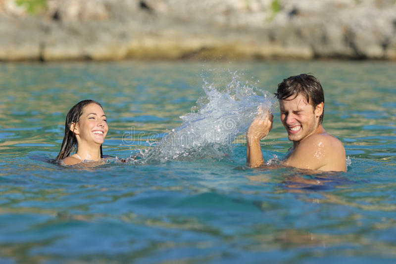Koppla ihop att spela badning på stranden i sommarsemester royaltyfri foto
