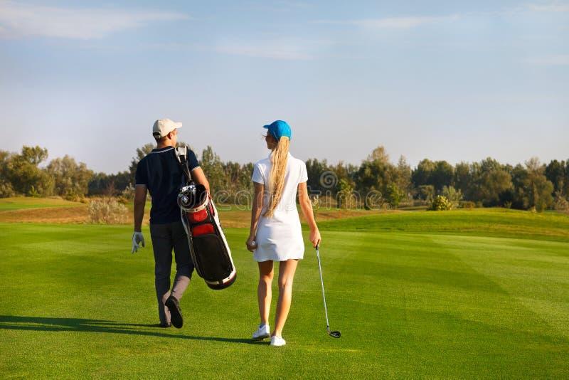 Koppla ihop att spela golf på en golfbana som går till det nästa hålet royaltyfria bilder
