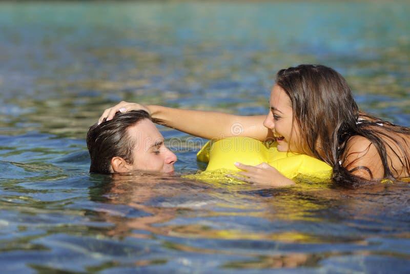 Koppla ihop att spela på stranden i sommarsemester fotografering för bildbyråer