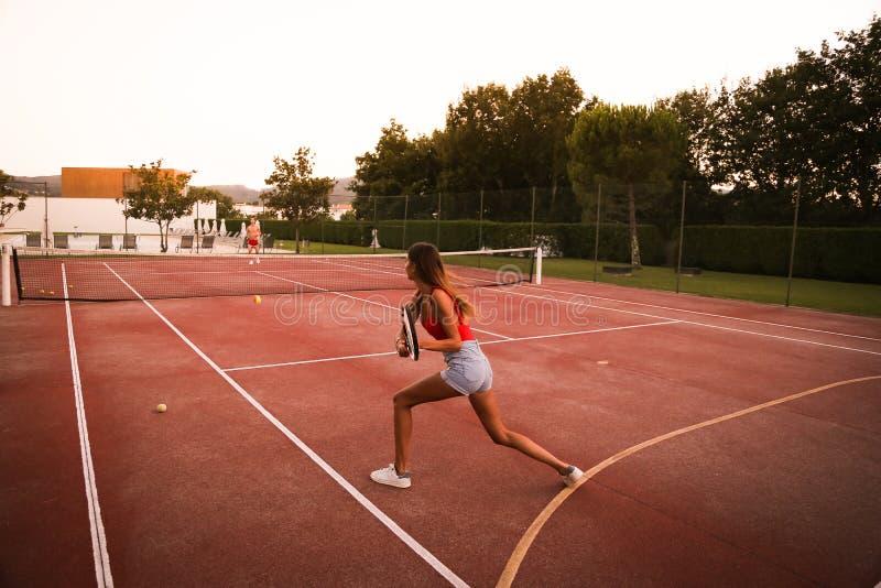 Koppla ihop att spela tennis på domstolen royaltyfri foto