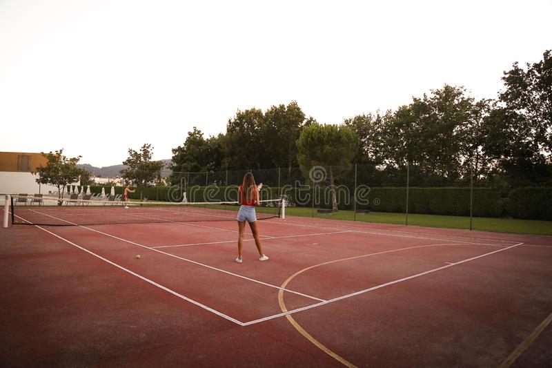 Koppla ihop att spela tennis på domstolen royaltyfri fotografi
