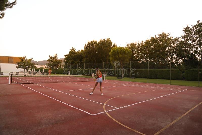 Koppla ihop att spela tennis på domstolen royaltyfria foton