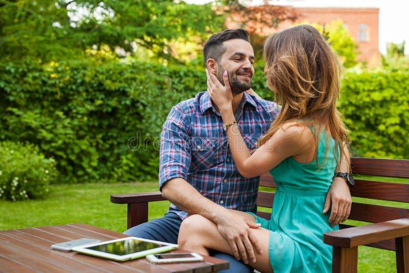 Koppla ihop att spendera stor tid på filten i trädgården royaltyfri bild