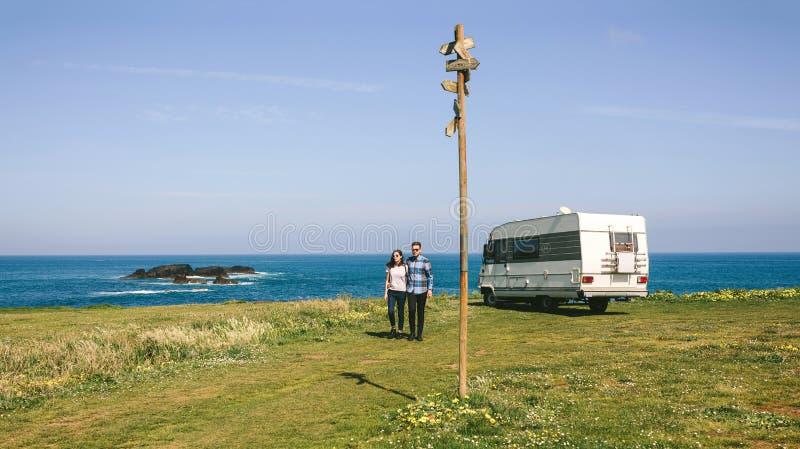 Koppla ihop att ta en g? n?ra kusten med en campare arkivfoton