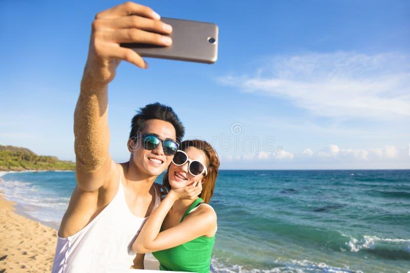 koppla ihop att ta semesterselfiefotografiet på stranden royaltyfri foto