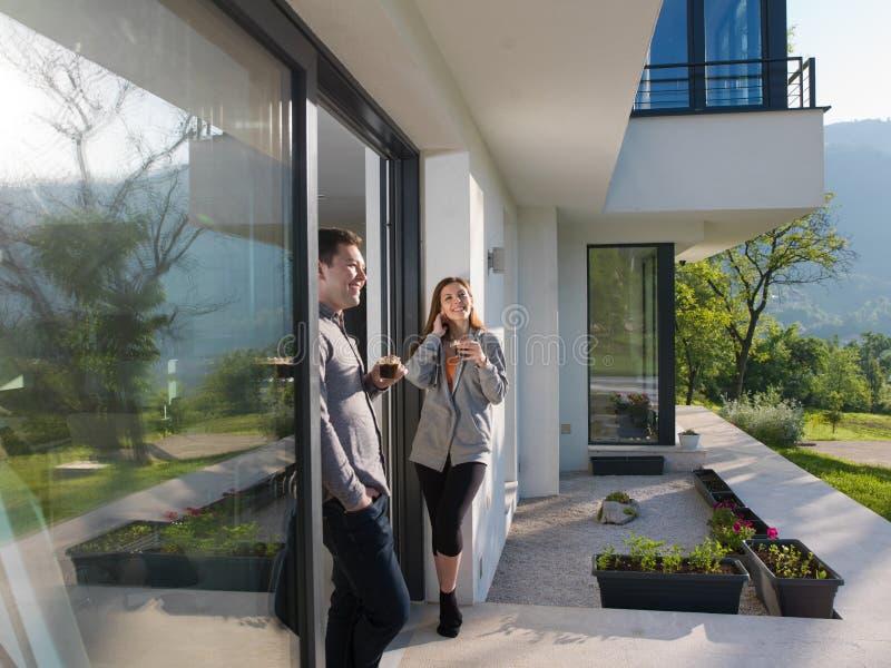 Koppla ihop att tycka om på dörren av deras lyxiga hem- villa arkivfoto