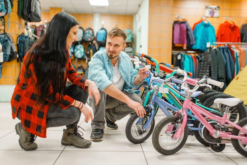 Koppla ihop att välja barns cykel som shoppar fotografering för bildbyråer
