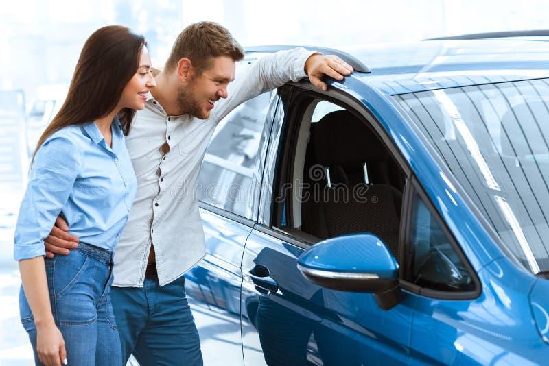 Koppla ihop att välja en bil på bilsalongen royaltyfria bilder