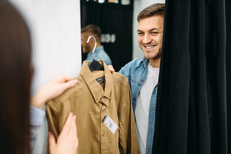 Koppla ihop att välja skjortor i provhytt, lager royaltyfri foto