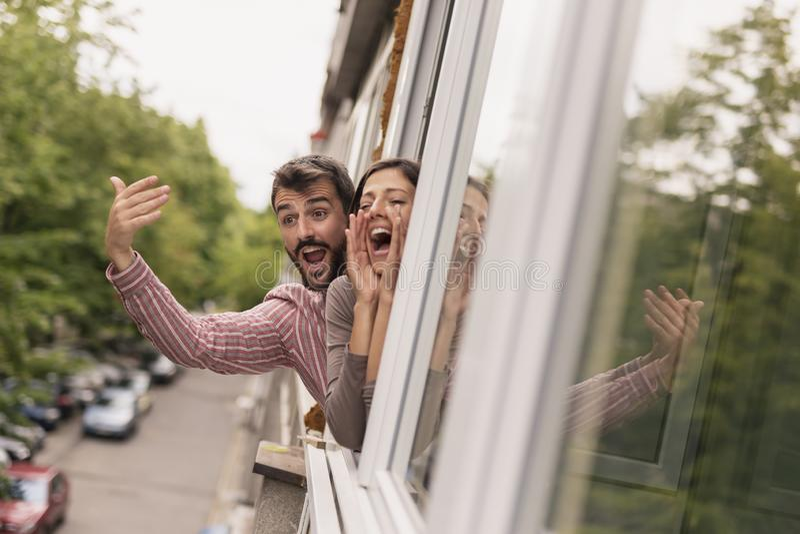 Koppla ihop att vinka och att ropa till och med ett öppnat fönster fotografering för bildbyråer