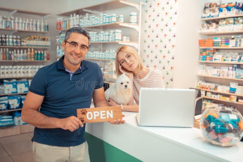 Koppla ihop av entreprenörer som hälsar kunder, når du har öppnat husdjuret, shoppar arkivfoto
