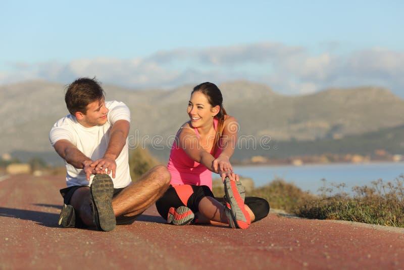 Koppla ihop av löpare som sträcker ben efter sport arkivbilder