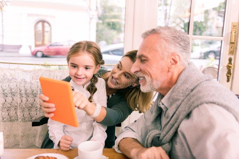 Koppla ihop av morföräldrar som håller ögonen på tecknade filmer på minnestavlan med deras gulliga flicka fotografering för bildbyråer