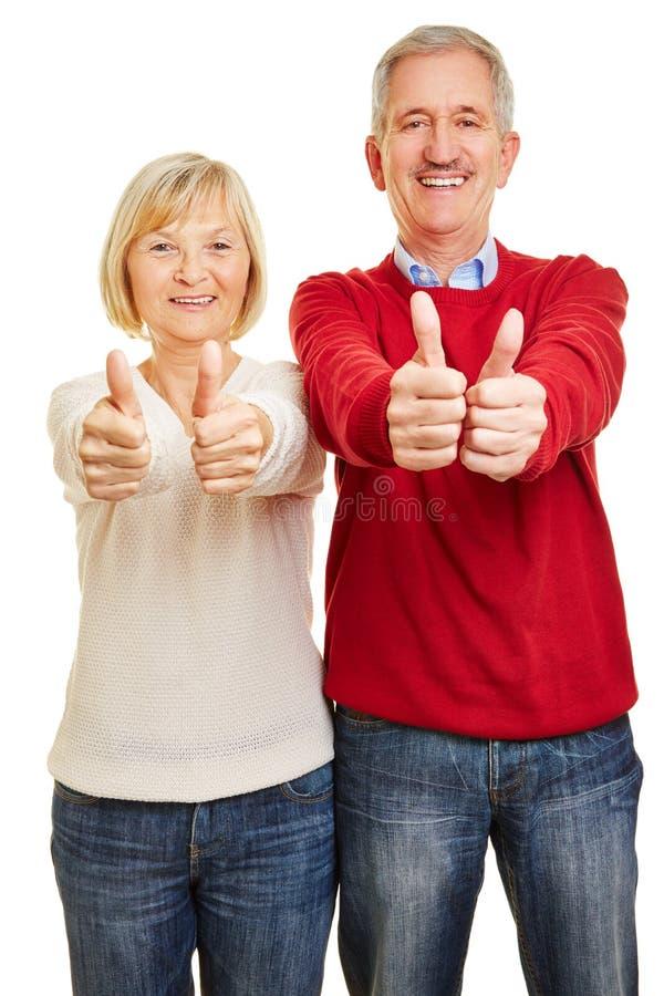 Koppla ihop av pensionärer håller upp båda tummar arkivfoto