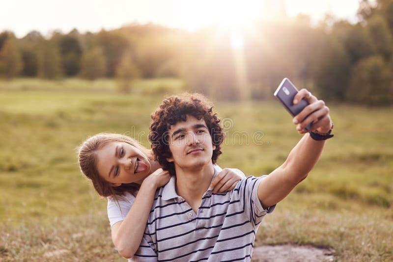 Koppla ihop av tonåringar har gyckel tillsammans, att göra selfie, rymmer den smarta telefonen, showtungan, iklädd tillfällig drä royaltyfria bilder