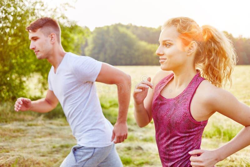 Koppla ihop av tonåringar som tillsammans joggar royaltyfri foto