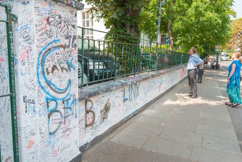 Koppla ihop av turister på Abbey Road utanför berömda studior som ser över den dolda väggen för grafitti royaltyfria foton