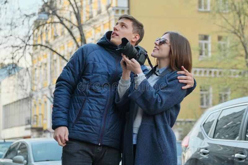 Koppla ihop av turister som går i staden, ung härlig man och kvinnan som tar bilder på fotokameran, bakgrundsstad i vår royaltyfri fotografi