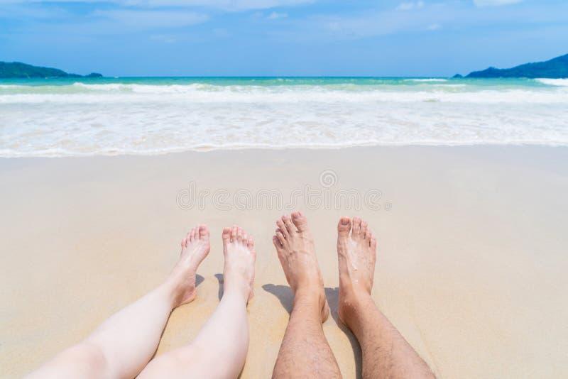Koppla ihop ben som solbadar nära stranden under lopp, semestrar semesterdet fria på havet eller naturhavet på middagen, Phuket,  arkivfoto