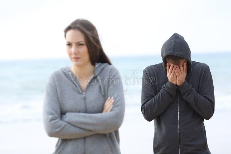 Koppla ihop bryter upp på stranden med en flicka som lämnar mannen fotografering för bildbyråer