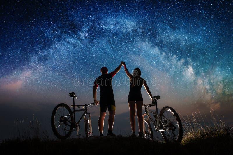 Koppla ihop cyklister med mountainbiken på natten under stjärnklar himmel royaltyfri bild