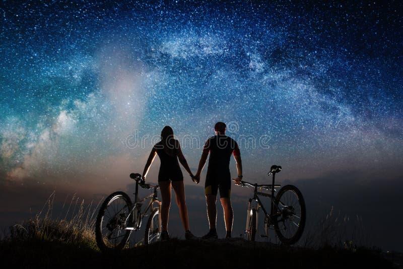 Koppla ihop cyklister med mountainbiken på natten under stjärnklar himmel royaltyfria bilder