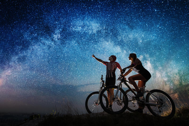 Koppla ihop cyklister med mountainbiken på natten under stjärnklar himmel royaltyfria foton