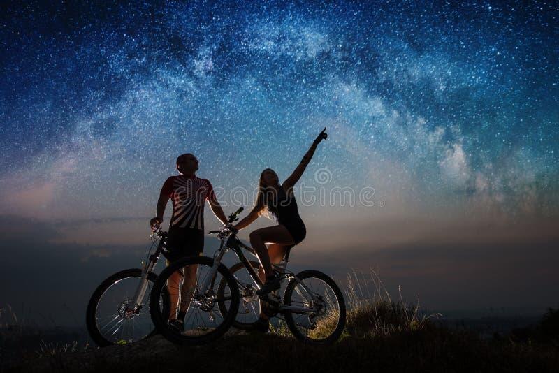 Koppla ihop cyklister med mountainbiken på natten under stjärnklar himmel fotografering för bildbyråer