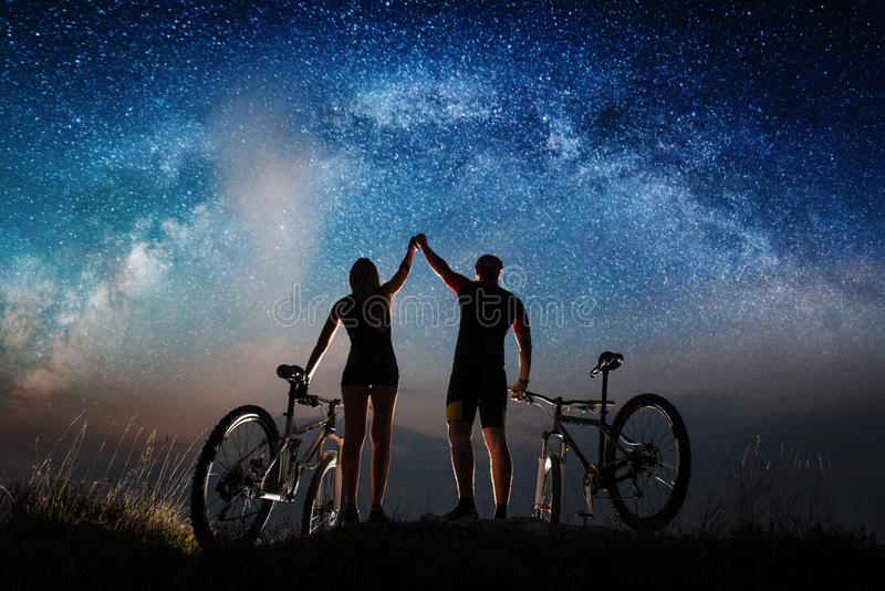 Koppla ihop cyklister med mountainbiken på natten under stjärnklar himmel royaltyfri foto