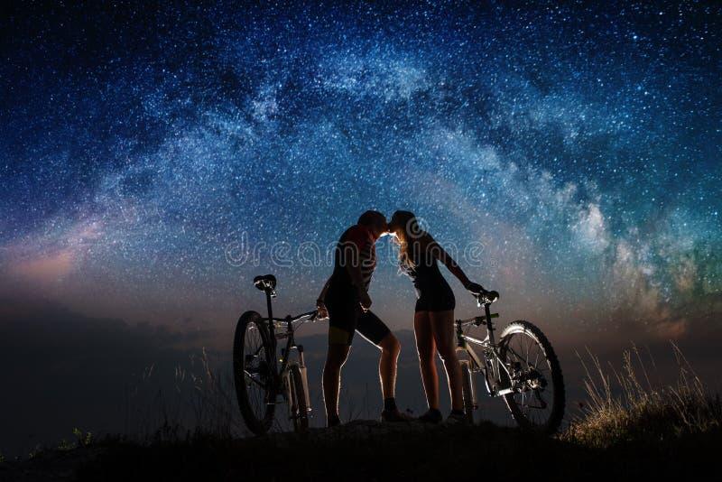 Koppla ihop cyklister med mountainbiken på natten under stjärnklar himmel arkivfoton