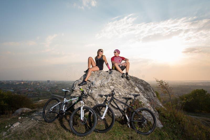 Koppla ihop cyklister som sitter på stenen nära, cyklar i aftonen royaltyfria bilder