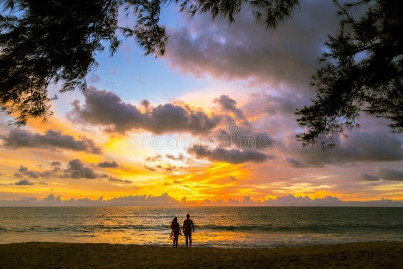 Koppla ihop den förälskade hållande ögonen på solen på solnedgången på stranden, Phuket Thaila royaltyfri foto