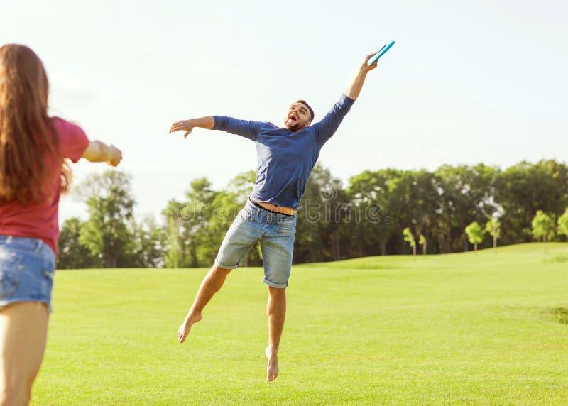 Koppla ihop den förälskade spela frisbeen i parkera, begreppet av en hea fotografering för bildbyråer