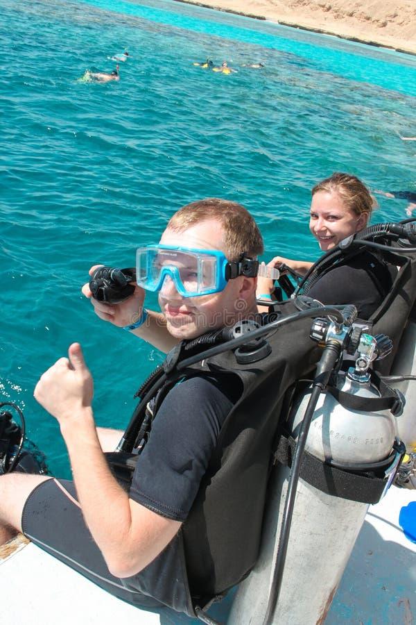 Koppla ihop dykare som förbereder sig att dyka från fartyget på sommardag royaltyfri foto