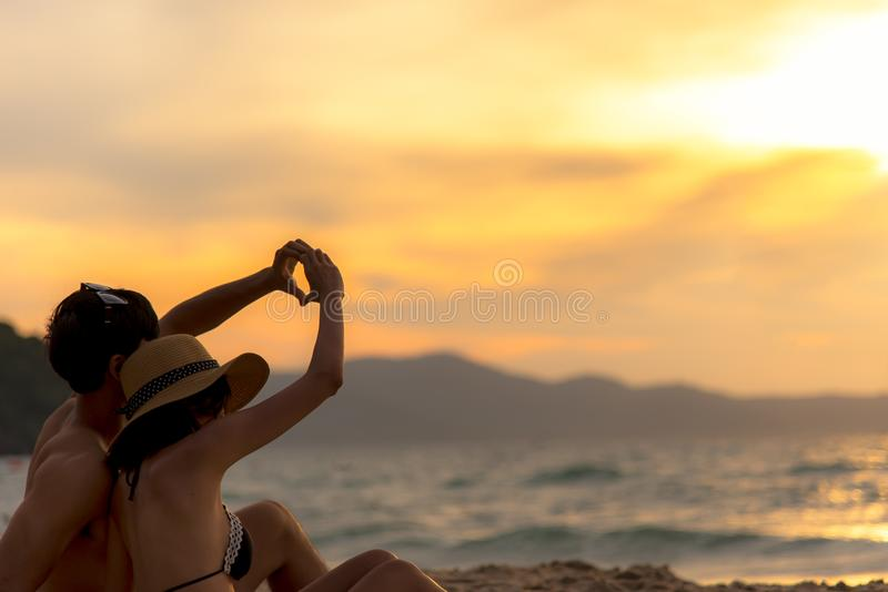 Koppla ihop förälskad danande en hjärta - forma med händer på tropiskt på solnedgångstranden i ferie royaltyfri foto