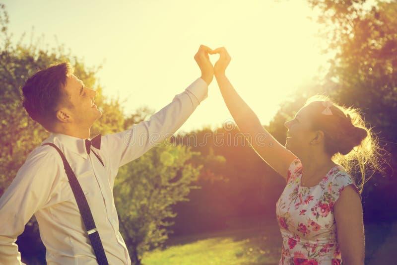 Koppla ihop förälskad danande en hjärtaform med deras händer i solsken arkivbilder