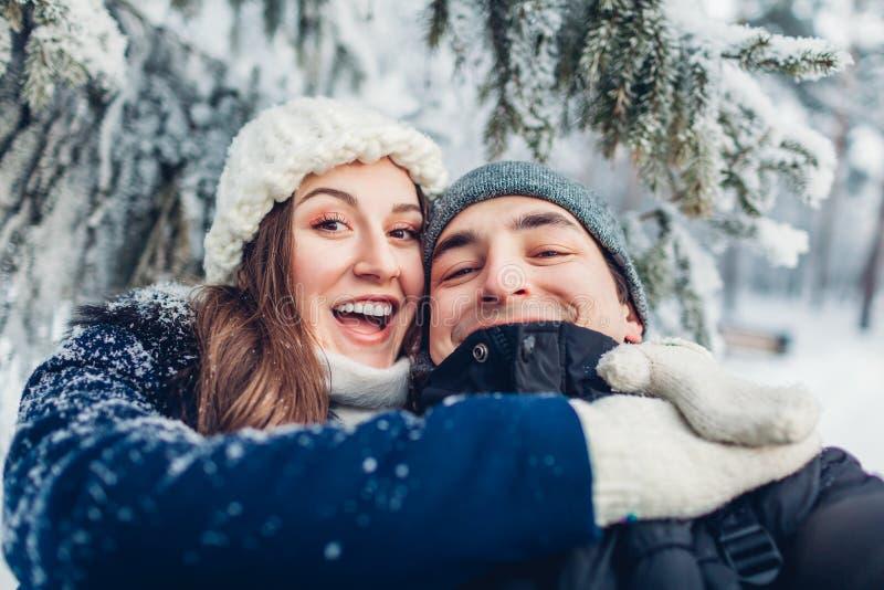 Koppla ihop förälskad tagande selfie och att krama i ungt lyckligt folk för vinterskogen som har gyckel valentin för dag s arkivfoto