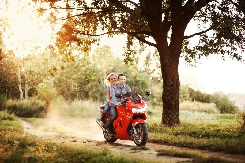 Koppla ihop förälskade ritter en motorcykel i parkera arkivbild