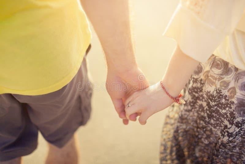 Koppla ihop förälskade rymmande händer i solljus close upp arkivbilder