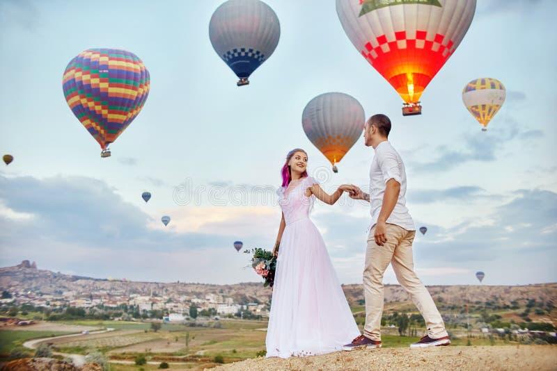 Koppla ihop förälskade ställningar på bakgrund av ballonger i Cappadocia Man och en kvinna på kulleblick på ett stort antal flygb arkivfoton