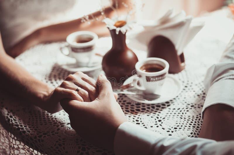 Koppla ihop förälskat drinkkaffe i kafét som rymmer varje - annat handen arkivbilder