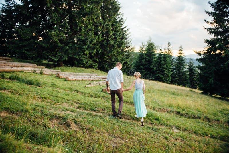 Koppla ihop förälskat gå i bergen och att ha gyckel royaltyfria foton