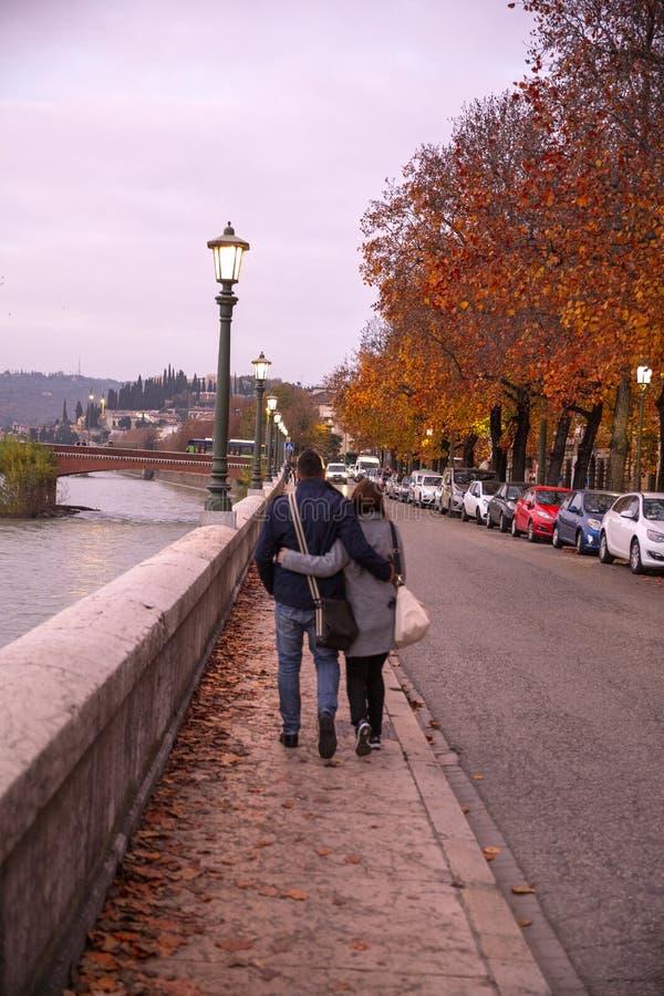 Koppla ihop förälskat gå i höstgatorna av Verona Stilfulla unga par som går på europeiska höstgator, har roligt och arkivfoto