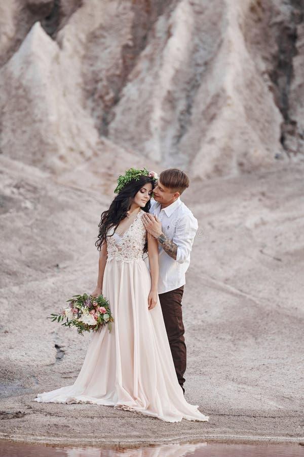 Koppla ihop förälskat i sagolika berg som kramar, marsinvånarelandskap Vänner går i bergen i sommaren royaltyfri fotografi