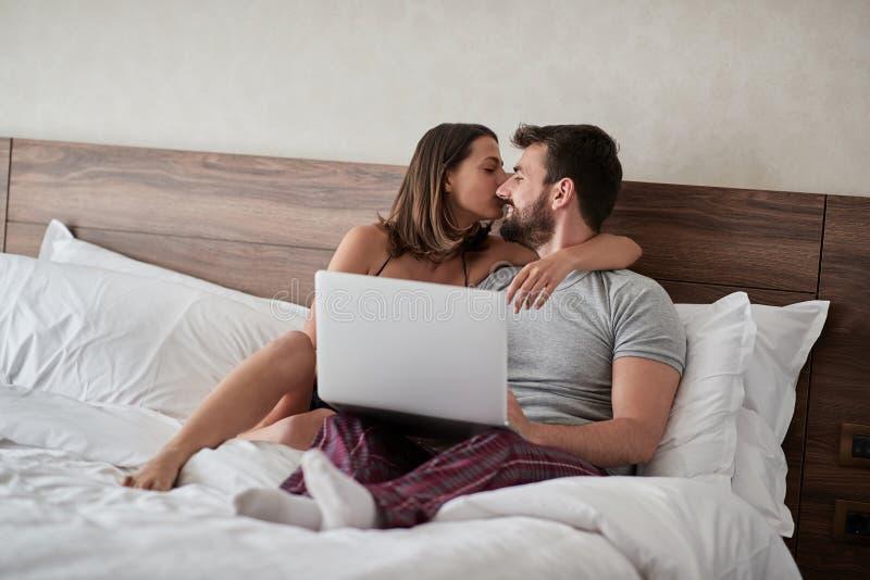 Koppla ihop förälskat kyssa - passionerade vänner som har romantiska och intima ögonblick på sängen - könsbestämmer och passionbe royaltyfri bild